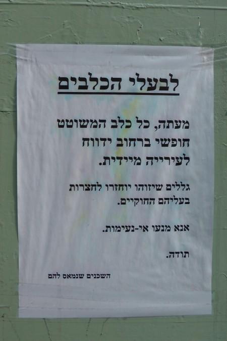 """שלט בתל אביב: """"לבעלי הכלבים. מעתה, כל כלב המשוטט חופשי ברחוב ידווח לעירייה מיידית. גללים שיזוהו יוחזרו לחצרות בעליהם החוקיים. אנא מנעו אי-נעימות. תודה. השכנים שנמאס להם"""". צילום: ירון ברוידא"""