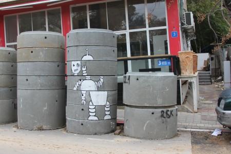 גרפיטי רובוט של Imaginery Duck על צינורות ביוב, רחוב נפחא, תל אביב. צילום: עידו קינן, חדר 404, cc-by-sa