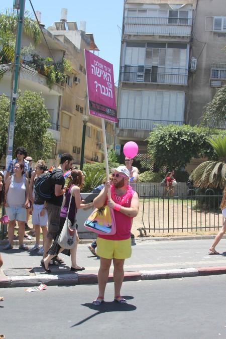 איש לבוש בורוד נושא שלט, אז מי אצלכן האישה ומי הגבר, מצעד הגאווה בתל אביב, 8.6.2012. צילום: עידו קינן