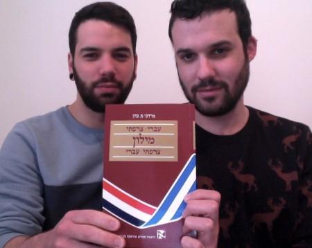 איל קסירר ובן זוגו עומר בן-ארצי עם המילון הצרפתי-עברי/עברי-צרפתי. צילום באדיבות קסירר