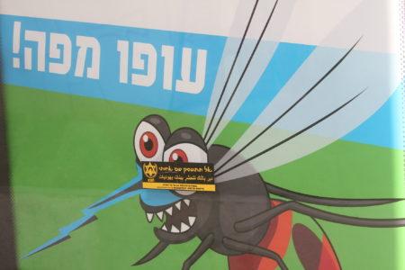 """מדבקת """"אל תתעסק עם אחותי"""" של להב""""ה נגד זוגיות של יהודיות עם ערבים מודבקת על מודעת """"עופו מפה"""" של עיריית תל אביב נגד יתושים. צילום: עידו קינן"""