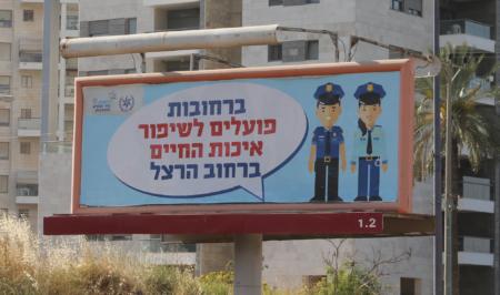 """שלט חוצות עם איור שוטרים לצד הכיתוב """"ברחובות פועלים לשיפור איכות החיים ברחוב הרצל"""" ברחובות, 4.2016. צילום: עידו קינן"""