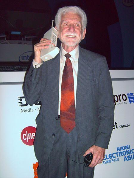 """ד""""ר מרטין קופר, ממציא הטלפון הסלולרי, מציג את האבטיפוס DynaTAC שנבנה ב-1973, באירוע ב-2007. תמונה: Rico Shen (cc-by-sa)"""