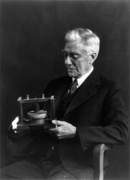 תומאס ווטסון, שותפו של אלכסנדר גרהאם בל להמצאת הטלפון, מחזיק בדגם של הטלפון הראשון של בל. תמונה בנחלת הכלל