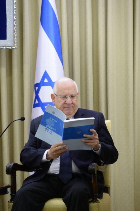 """נשיא המדינה ראובן ריבלין קורא את דוח בנק ישראל, 27.3.2017. תמונה: מארק ניימן/לע""""ם"""