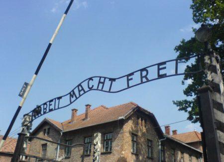 """שלט """"העבודה משחררת"""" בכניסה למחנה ההשמדה אושוויץ. תמונה: Neil (cc-by-sa)"""